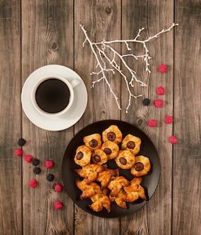 Verticaal bovenaanzicht van een bord met kwarkkoekjes en een kopje koffie