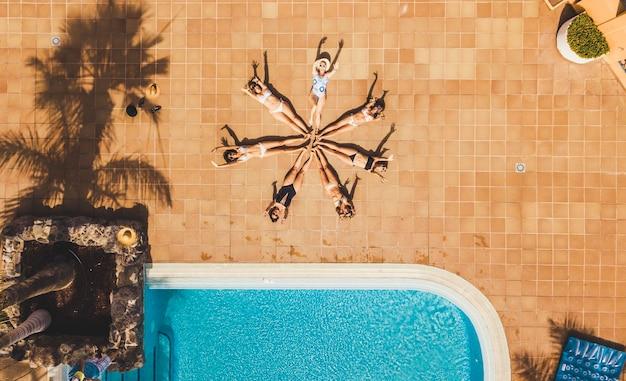 Verticaal bovenaanzicht van een groep vrouwelijke jonge vrienden die samen met hun lichaam een ster vormen