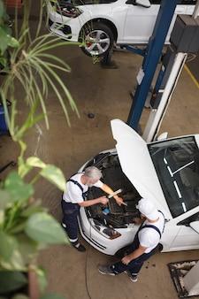 Verticaal bovenaanzicht van twee monteurs die in de garage aan een auto werken