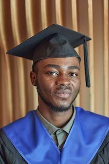 Verticaal close-up portret van een afro-amerikaanse jongeman met een afstudeerjurk en een hoed die naar de camera glimlacht terwijl hij binnenshuis poseert