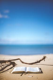 Verticaal close-upschot van een open bijbel op een strandkust overdag