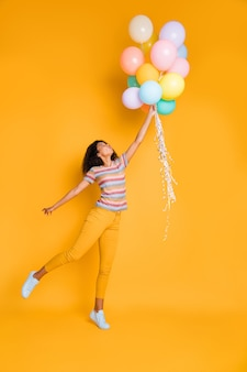 Verticaal dromerig meisje in gestreept t-shirt met luchtballen
