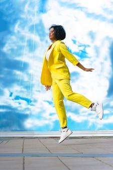 Verticaal frame, donkere vrouw in een sprong, springend tegen een achtergrond van heldere hemel. mooie afro-amerikaanse zwarte zakenvrouw