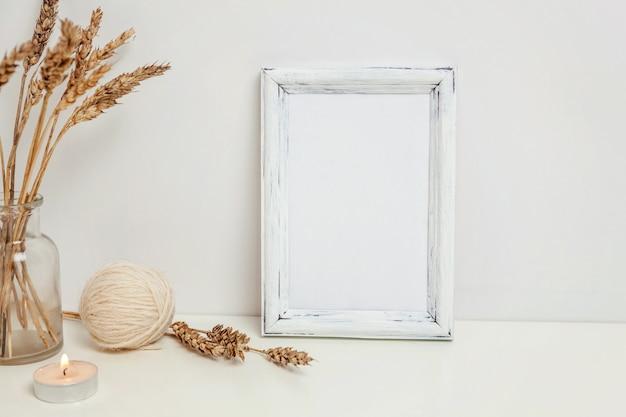 Verticaal framemodel met wild roggeboeket in glazen vaas in de buurt van witte muur. leeg frame mock-up voor presentatieontwerp. sjabloon inlijsten voor moderne kunst. hygge scandinavische stijl natuurlijke eco-huisinrichting