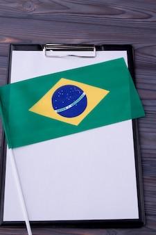 Verticaal geschoten braziliaanse vlag op klembord met blanco papier voor kopieerruimte