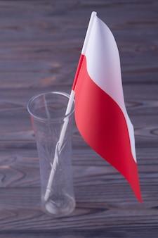 Verticaal geschoten rode en witte vlag van polen in de glazen vaas