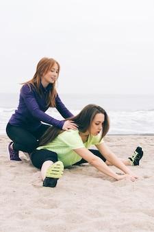 Verticaal gewas van jonge atletische vrouw die sportenoefeningen op het strand in bewolkt weer doet