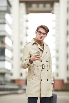 Verticaal grafisch portret van moderne jonge zakenman die trenchcoat draagt en smartphone houdt die naar camera loopt terwijl hij naar zijn werk reist in de stedelijke omgeving