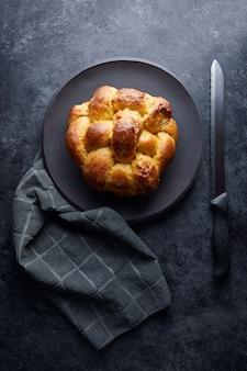 Verticaal hoog hoekschot van vers gebakken gebakje in een zwarte plaat dichtbij een mes op een zwarte oppervlakte