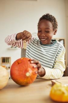 Verticaal middelgroot portret van vrolijke jonge jongen die pompoen met keukenmes snijden tijdens het voorbereiden van halloween