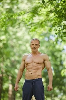 Verticaal middellang geschoten portret van sterke sportieve man met gespierde lichaamsbouw staande shirtless buitenshuis camera kijken