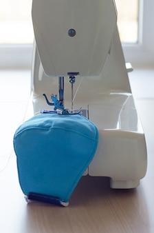 Verticaal, naai een medisch gezichtsmasker tijdens de periode van influenza, epidemie, pandemie van coronavirus, zachte focus