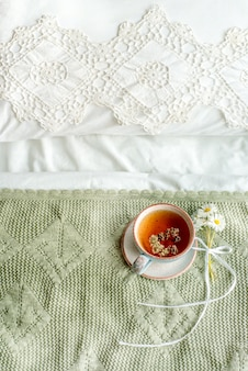 Verticaal, olijf plaid, kopje natuurlijke kruidenthee van munt en citroenmelisse in bed, ochtend close-up. gezellige sfeer. opengewerkte kant, katoenen witte deken, zomerse madeliefjebloemen. provence en retro stijl.