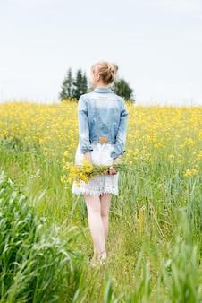 Verticaal portret mooi blonde meisje op een gebied van madeliefjes. vrouw in een witte jurk in een veld met gele bloemen. boeket madeliefjes. zomerdorp. wilde bloemen. gaat terug, een boeket achter.