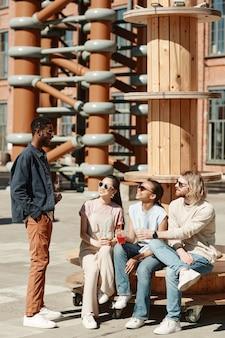 Verticaal portret over de volledige lengte van een diverse groep jonge mensen die aan het chatten zijn terwijl ze aan het relaxen zijn in een stedelijke stadsomgeving