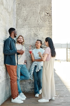 Verticaal portret over de volledige lengte van een diverse groep jongeren die chatten in een stedelijke stadsomgeving