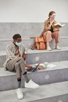 Verticaal portret over de volledige lengte van twee jonge studenten die werken en ontspannen terwijl ze in de grafische universiteitslounge zitten
