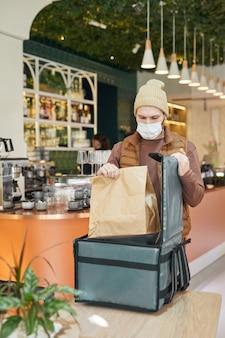 Verticaal portret van bezorger die een masker draagt tijdens het inpakken van afhaalbestellingen om in het café-interieur te verpakken