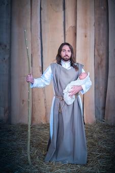 Verticaal portret van de figuur van jozef die jezus baby vasthoudt in een lgbt-kerststal