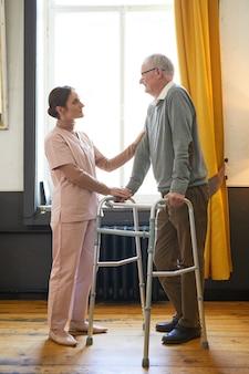 Verticaal portret van de volledige lengte van een glimlachende jonge vrouw die een oudere man helpt met een rollator in een verpleeghuis