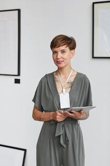 Verticaal portret van de vrouwelijke manager van de kunstgalerie die een digitale tablet vasthoudt en een tentoonstelling plant