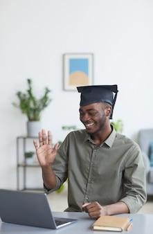 Verticaal portret van een afro-amerikaanse jongeman die een afstudeerpet draagt en naar de camera zwaait terwijl hij nieuws deelt met vrienden en familie via videochat, kopieer ruimte