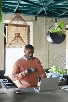 Verticaal portret van een afro-amerikaanse man die een laptop gebruikt en geniet van koffie terwijl hij in een milieuvriendelijk café-interieur werkt, versierd met verse groene planten