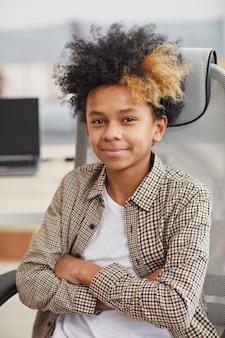 Verticaal portret van een afro-amerikaanse tienerjongen die naar de camera glimlacht terwijl hij in de stoel zit tegen de computer op de achtergrond