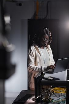 Verticaal portret van een afro-amerikaanse vrouwelijke netwerkingenieur die een laptop gebruikt terwijl hij in een donkere serverruimte werkt