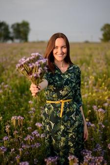 Verticaal portret van een gelukkig meisje in een veld bij zonsondergang strekt zich uit een boeket veld paarse bloemen, glimlachend