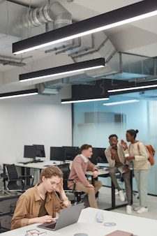 Verticaal portret van een gestresste jonge vrouw die een laptop gebruikt in een kantoor- of coworkingruimte met een groep mensen op de achtergrond, kopieer ruimte