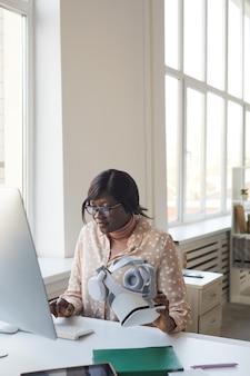 Verticaal portret van een jonge afro-amerikaanse vrouw die computer gebruikt terwijl ze alleen aan een bureau werkt in een modern wit kantoor, kopieer ruimte