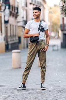 Verticaal portret van een jonge man die opzij kijkt, afgeleid voor de camera met vrijetijdskleding