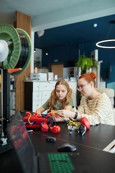 Verticaal portret van een jonge vrouwelijke leraar die een meisje helpt bij het bouwen van een robot tijdens de techniekles op de moderne school