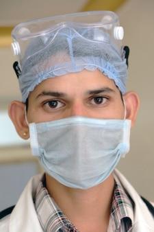 Verticaal portret van een jonge zuid-aziatische mannelijke arts met een beschermend masker