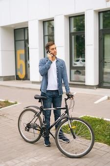 Verticaal portret van een knappe jongeman in casual kleding die met de fiets in de straat van de stad staat en op de mobiele telefoon praat. zelfverzekerd fietsermannetje dat buiten op mobiel spreekt door stedelijk gebouw.