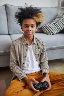 Verticaal portret van een lachende afro-amerikaanse jongen die thuis videogames speelt en naar de camera kijkt terwijl hij de gamepad vasthoudt en op de vloer zit