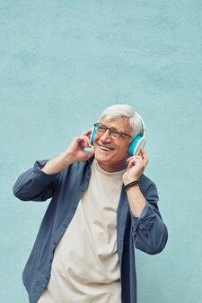 Verticaal portret van een moderne senior man die naar muziek luistert en glimlacht terwijl hij een grote koptelefoon draagt tegen een blauwe achtergrond