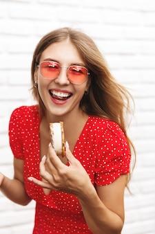 Verticaal portret van een mooi meisje dat roomijs eet en camera bekijkt.