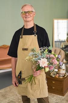 Verticaal portret van een senior mannelijke bloemist die een boeket vasthoudt terwijl hij in de bloemenwinkel staat en een...