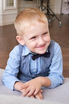 Verticaal portret van een vijfjarige blonde jongen in een overhemd, vest en vlinderdas