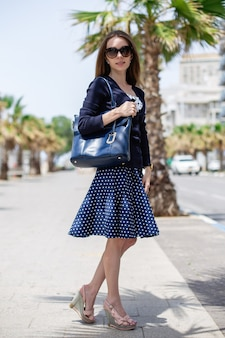 Verticaal portret van een vrouw die een zak houdt en een zonnebril draagt