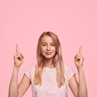 Verticaal portret van gelukkig jong vrouwtje heeft lang haar, punten met twee wijsvingers bovenaan