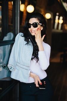 Verticaal portret van glamouronderneemster met donker luxueus haar die zonnebril en formele kleding dragen