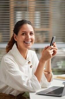Verticaal portret van glimlachende elegante vrouw die camera bekijkt en smartphone houdt terwijl u geniet van werk vanuit huis