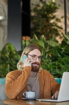 Verticaal portret van hedendaagse bebaarde zakenman die via smartphone spreekt en laptop gebruikt terwijl hij aan een cafétafel werkt in een groen, milieuvriendelijk interieur versierd met planten