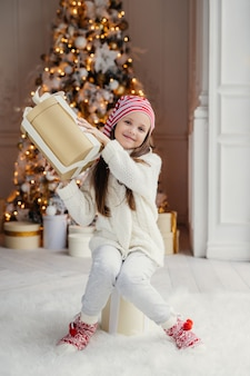 Verticaal portret van heerlijk klein vrouwelijk kind in witte kleding en warme sokken houdt grote huidige doos, ontvangt cadeau van ouders op nieuwjaar, vormt tegen gedecoreerde kerstboom