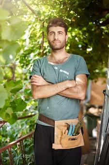 Verticaal portret van jonge aantrekkelijke bebaarde donkere boer in blauw t-shirt met tuingereedschap hand in hand gekruist, opzij kijkend met zelfverzekerde gezichtsuitdrukking.