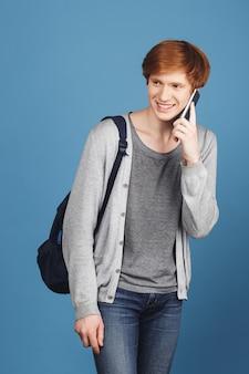 Verticaal portret van jonge knappe student met rood haar die toevallige uitrusting dragen en rugzak glimlachen, die op smartphone met vriend op weg naar universiteit spreken.