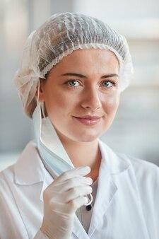 Verticaal portret van jonge vrouwelijke dokter lachend naar de camera tijdens het opstijgen van gezichtsmasker, kopieer ruimte